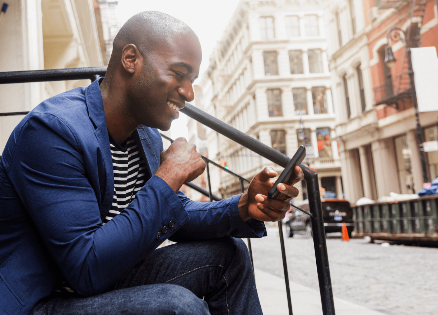 Man sitting outdoors using his phone.