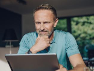 Man looking at tablet and thinking.