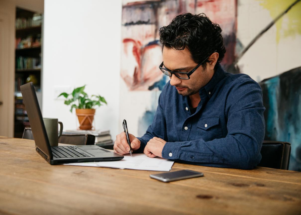 Man writing at a desk.