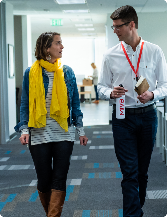 Two people walking in an office and talking.
