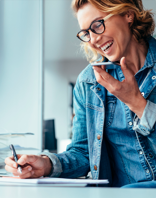 Woman writing while smiling on speakerphone.