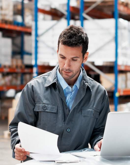 Man in warehouse looking at papers and laptop.