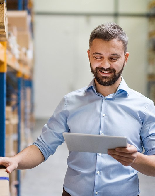 Man checking stock and looking at a tablet.